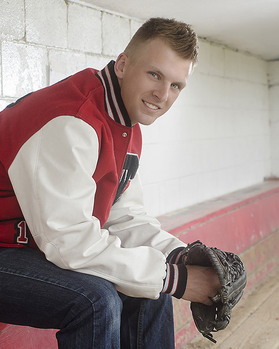 portrait of High School senior boy in dugout with baseball glove by Dan Cleary of Cleary Creative Photography in Dayton Ohio