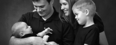 Young family holding 3 month old baby with baby brother looking on